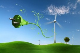 Grüner Stromstecker vor Windkraftrad